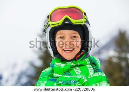 Skier, skiing, winter sport - portrait of Cute happy skier boy in a winter ski resort. - stock photo