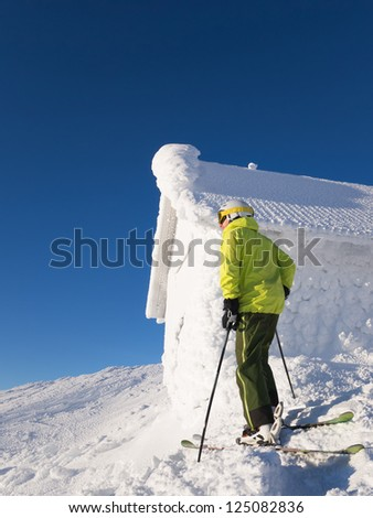 Skier standing next to cabin covered in frost.