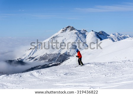 skier standing on top of a mountain above the clouds - stock photo