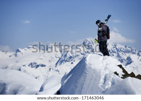 Skier stands at the top of a snowy peak over a blue sky,  - stock photo