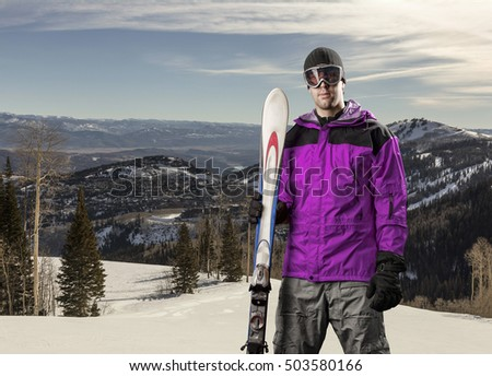 Skier with a pink jacket, holding a pair of skis on a snowy mountain.