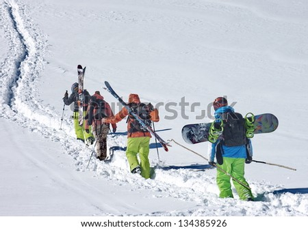Skiers and a snowboarder ascending a slope for free ride - stock photo