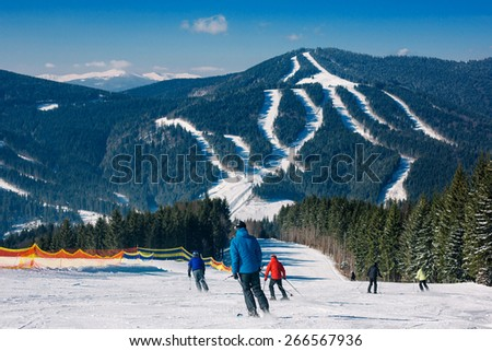 Skiers and snowboarders going down the slope at ski resort in Carpathian mountains, Ukraine - stock photo