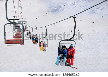 Skiers and snowboarders on a ski lift - stock photo