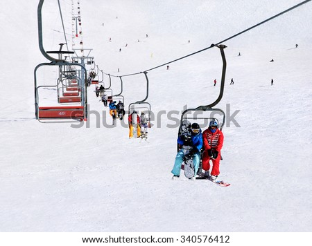 Skiers and snowboarders on a ski lift against winter snowy mountain landscape
