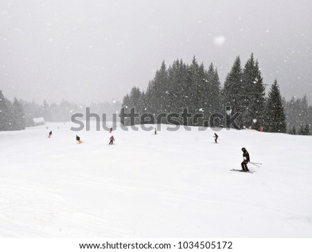 Skiers and snowboarders on the slope in the austrian alps. Winter landscape with on the slope with grey sky and mist while snowing. People skiing during intense snowfall. Ski resort in Austria, Europe