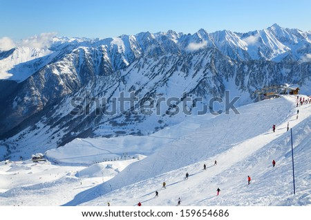 Skiers are sliding down snow-covered hill on skis at the Cirque du Lys. There is range of mountains (Soum de Mauloc) in the background. Winter Pyrenees is photographed at the Cauterets ski resort.  - stock photo