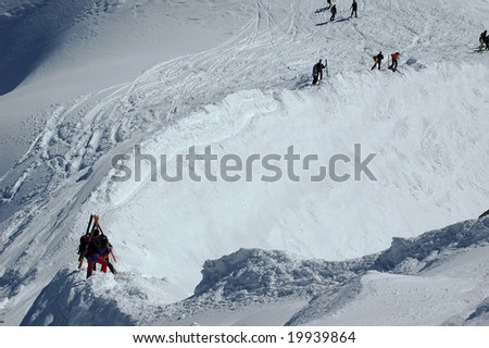 skiers carefully descending the knife edge ridge leading to the valley blanche from the aiguille du midi. A slip to the left means death.