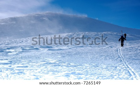 Skiers climning on top of mountain