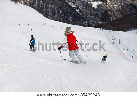 Skiers going down the slope - stock photo