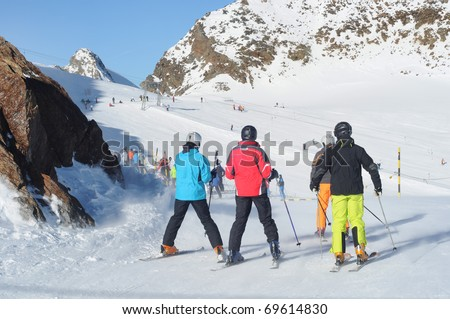 Skiers having fun on wide slopes of Austrian glacier in Solden.