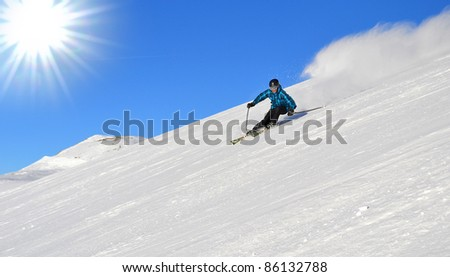 skiers in carving arc on the piste in the Alps in the sun - stock photo