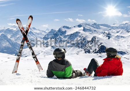 Skiers lying on snow in high mountains with cross ski, Alps - stock photo
