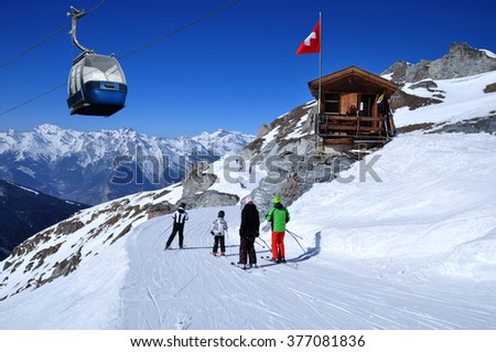 Skiers on the ski slope in Swiss Alps in sunny day. Small wooden house with red swiss flag. Blue cable car in skiing resort in mountains, Switzerland. - stock photo
