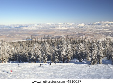Skiers on the slope above Nevada desert in Lake Tahoe area. Motion blur on one of fast moving skiers. - stock photo