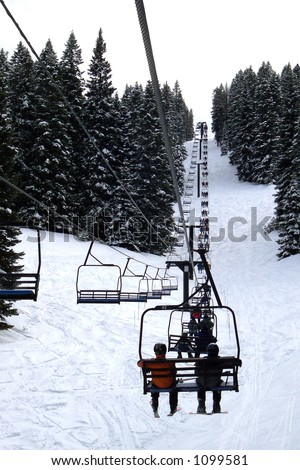 Skiers Riding Up a Chair Lift - stock photo