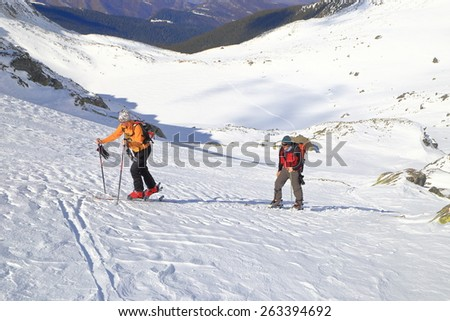 Skiers skinning uphill in sunny winter day - stock photo