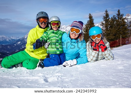 Skiers, sun and fun - Family with two kids enjoying winter vacations. - stock photo