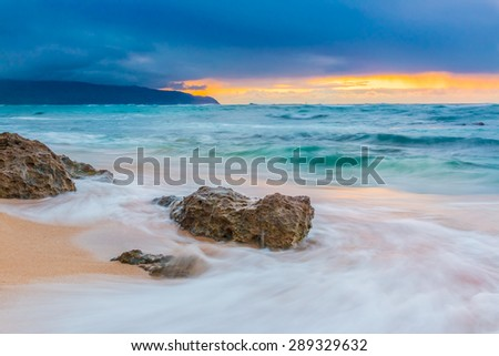 Skies on fire at sunset, with the rain in the background in North Shore, Oahu, Hawaii - stock photo
