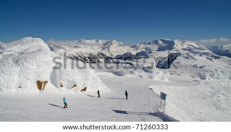 Skiing and snowboarding off the Peak of Whistler mountain in Canada - stock photo
