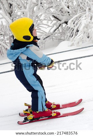 Skiing child on a children rope ski lift.  - stock photo