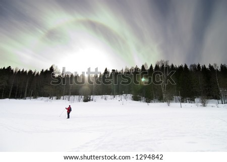 Skiing on a contrasty dramatic day.  A winter landscape looking into the sun with lens flare. - stock photo
