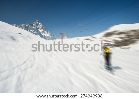 Skiing on snowy slope in scenic ski resort of the italian Alps, with bright sunny day of spring season and high mountain peak in the background. Radial blurred motion effect applied. - stock photo