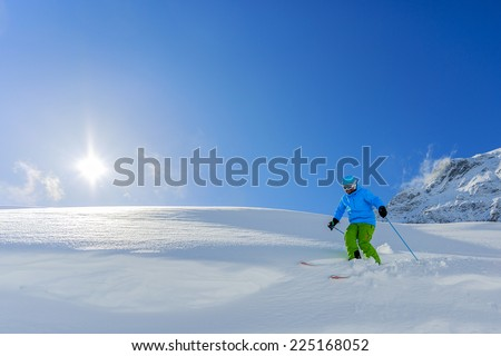 Skiing, Skier, Freeride in fresh powder snow - man skiing downhill - stock photo