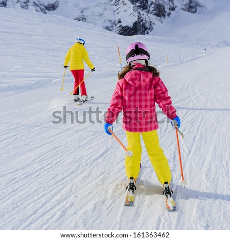 Skiing, skiers on ski run - female skiers skiing downhill,  child on ski lesson - stock photo