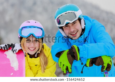 Skiing, snowboarding, winter sports - portrait of young skiers, couple having fun on ski - stock photo