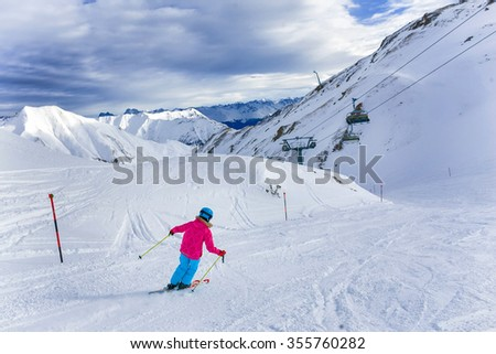 Skiing, winter, child - back view of young skier girl in helmet and goggles in winter resort