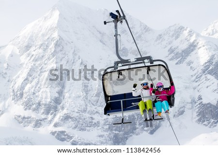 Skiing, winter - happy skiers on ski lift - stock photo