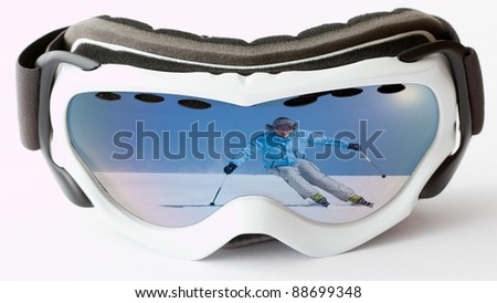 Skiing,winter - reflection of male skiing downhill in ski goggles - stock photo