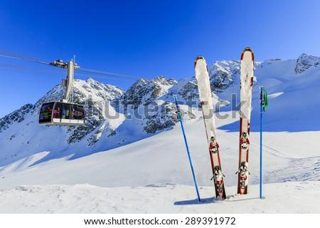 Skiing, winter season - mountains, cable car and ski equipments on ski run - stock photo