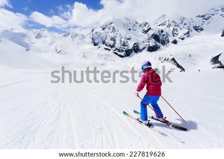 Skiing, winter sport - child skiing downhill - stock photo