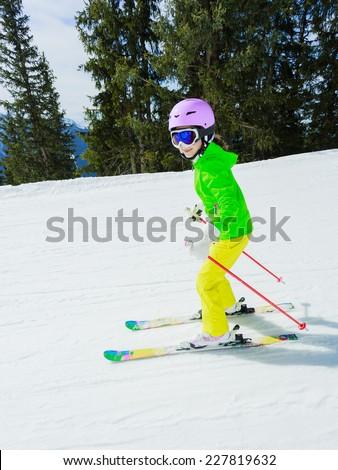 Skiing, winter sport - girl skiing downhill - stock photo