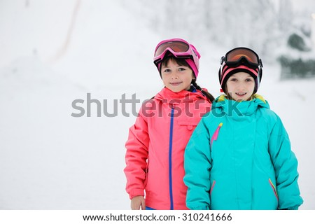 Skiing, winter sports - two adorable kid girls in colorful clothes and ski googles - stock photo