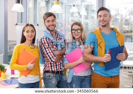 Skilful young colleagues are working together in cooperation. They are standing and holding folders of documents. The men and women are smiling. They are looking at camera happily - stock photo