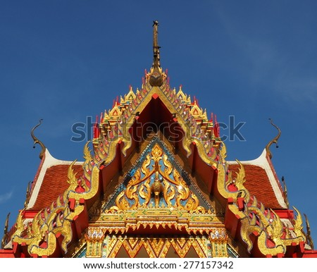 Skilfully crafted gable at Thai temple Wat Yai Sawang Arom soaring into blue sky