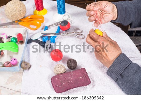 Skilled hands crafting leather balls for traditional pelota sport - stock photo