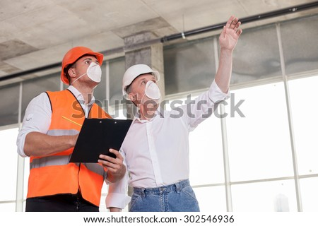 Skilled old architect is explaining to young foreman his ideas about project. He is pointing his arm sideways with aspirations. The foreman is writing down main concepts with concentration