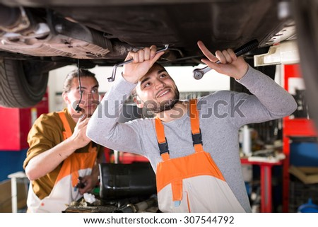 Skilled smiling mechanics in coveralls working under a lifted up car - stock photo