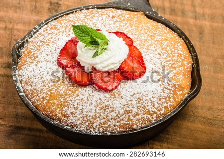 Skillet baked yellow cake with cream and red strawberries - stock photo