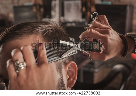 Skillful female hairdresser hairstyle hair of attractive man in hair salon. Close up. - stock photo