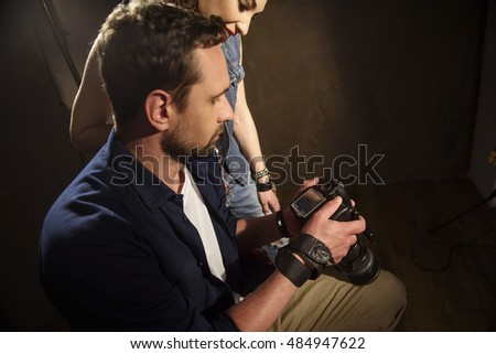 Skillful male photographer watching shots with woman