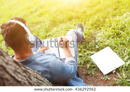 Skillful male student is making some notes - stock photo