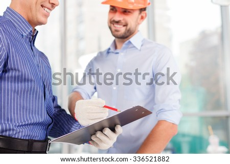 Skillful two architects are projecting new building. They are standing and smiling. The senior builder is holding a folder of document. The young man is pointing at the sketch - stock photo
