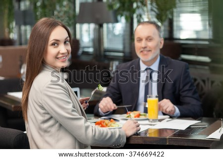 Skillful two managers are making a break in restaurant. They are sitting at the table and eating salad. The business partners are looking at camera and smiling - stock photo