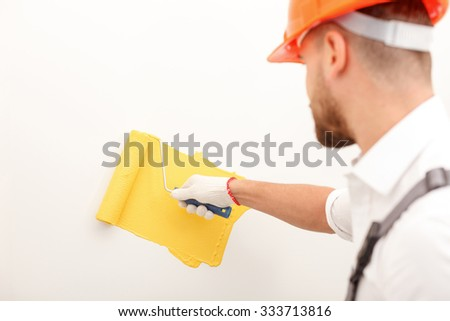 Skillful young builder is painting the wall. He is standing and holding a roller. The man is wearing an orange hardhead - stock photo