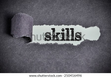 skills word under torn black sugar paper  - stock photo